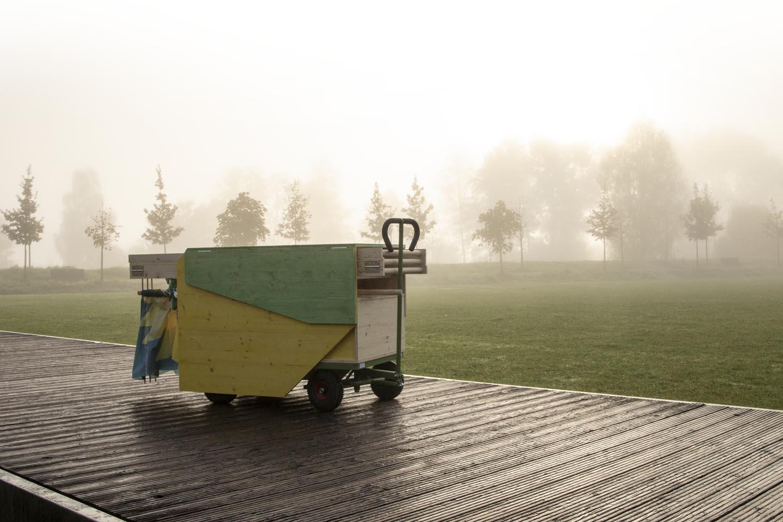 Holzwagen auf Rädern zusammengeklappt mit grüner Deichsel und schwarzen gubbi-Rädern